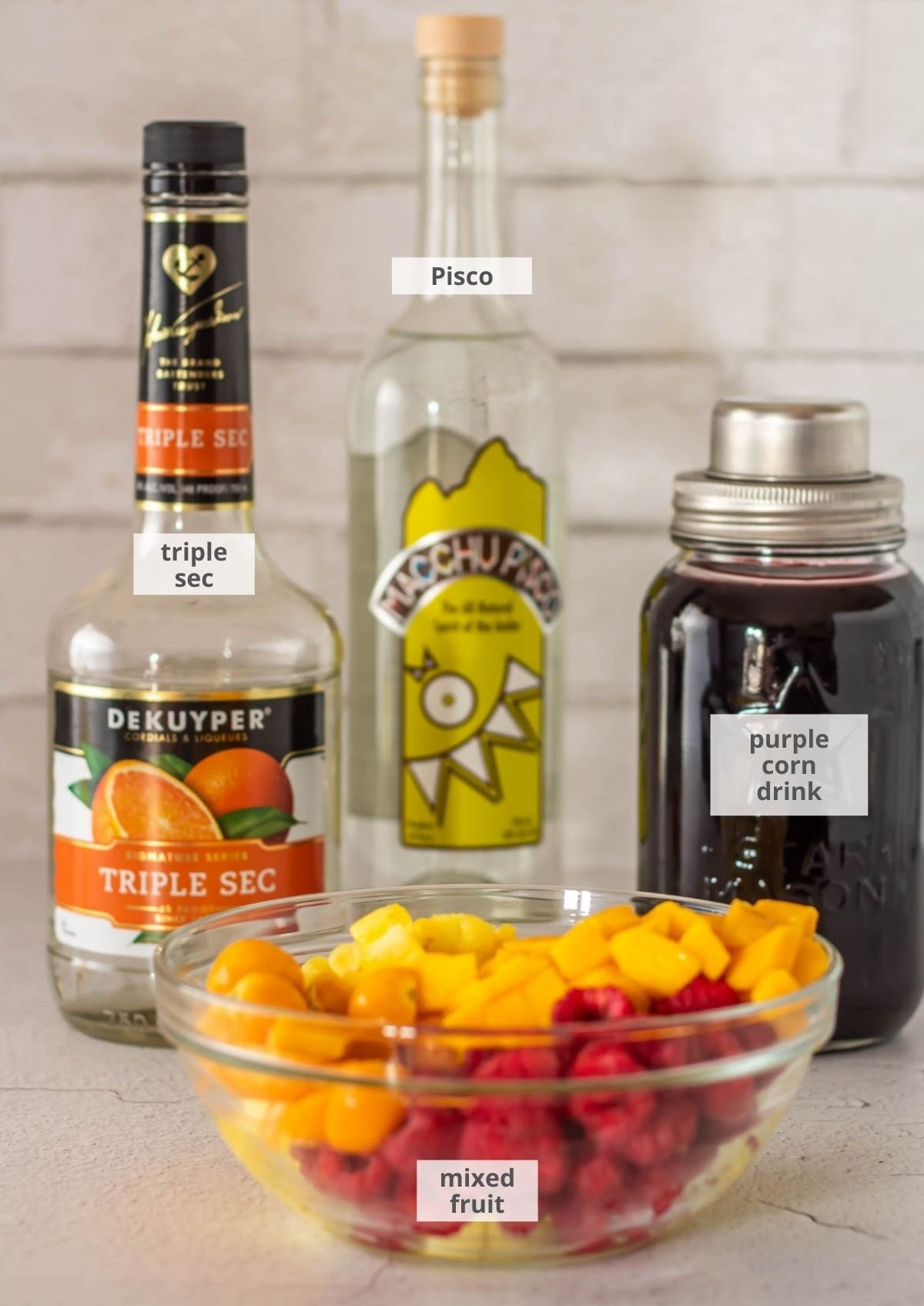 Ingredients for the Peruvian sangria: Orange liqueur, Pisco, chicha morada (purple corn drink), and mixed fruit.