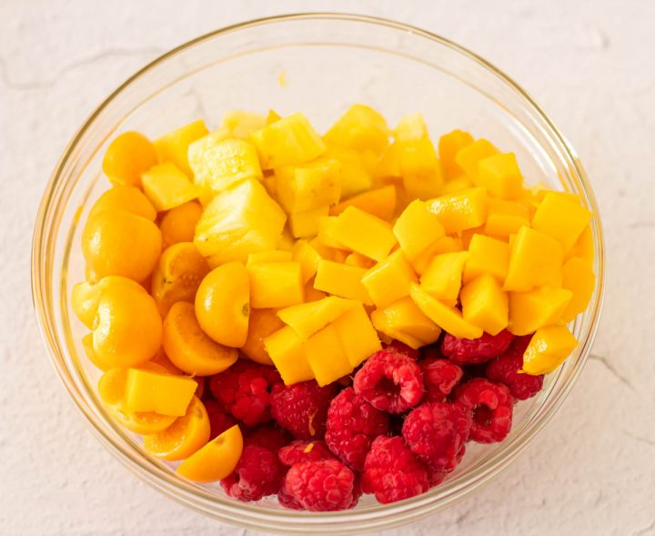 Mango, raspberries, pineapple, and goldenberries in a glass bowl for the Pisco Peruvian sangria.