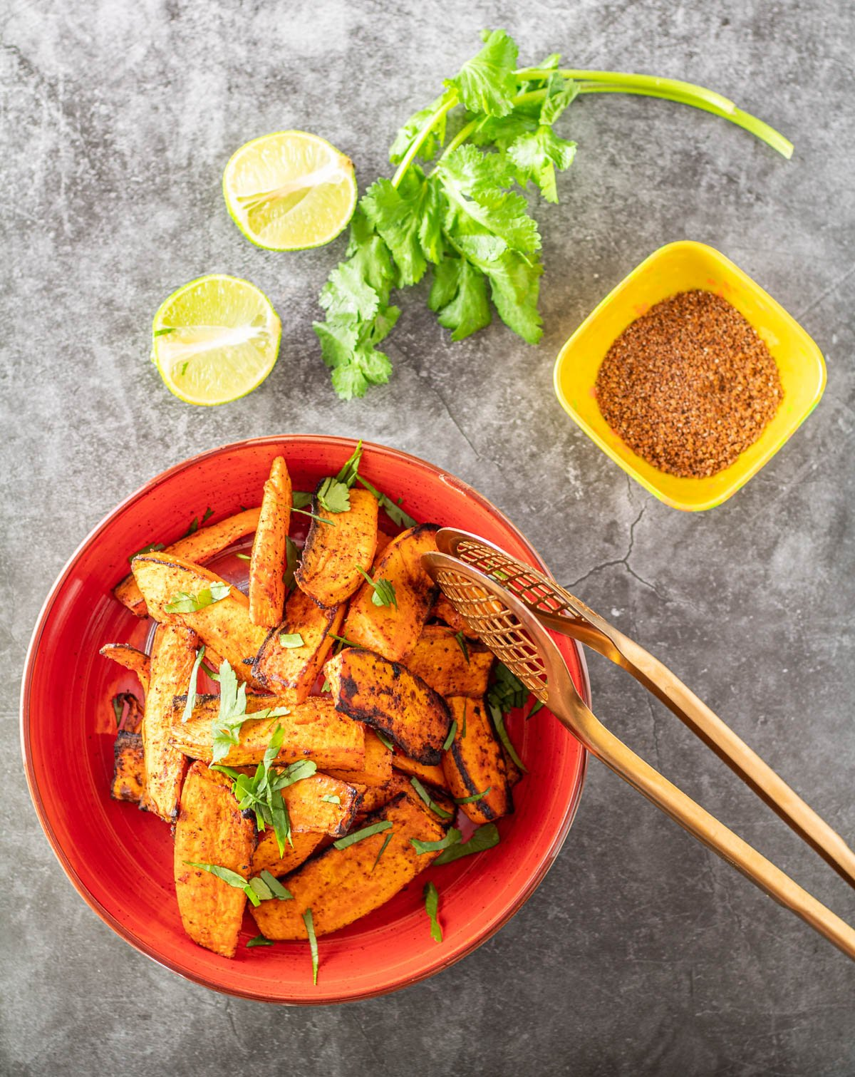 Air fryer sweet potato wedges in a red bowl with a bowl of tajin spice mix.