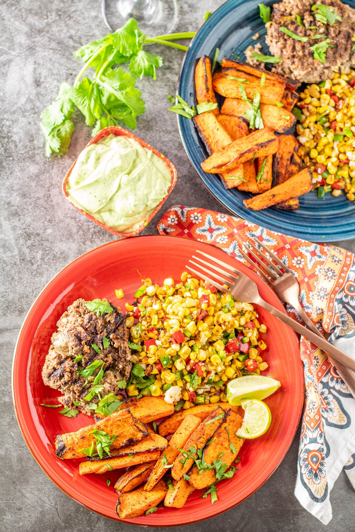 2 plates with sweet potato wedges, charred sweet corn, and bison patties, alongside a bowl of avocado crema.