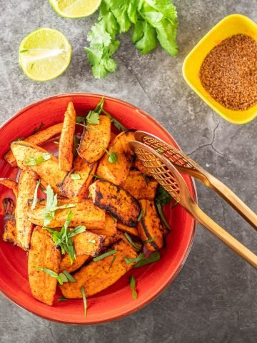 A red ceramic bowl with sweet potato wedges coated with tajin spice mix.