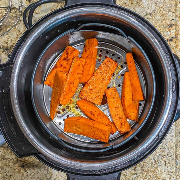 Air fryer basket with 2 layers of seasoned sweet potato wedges.