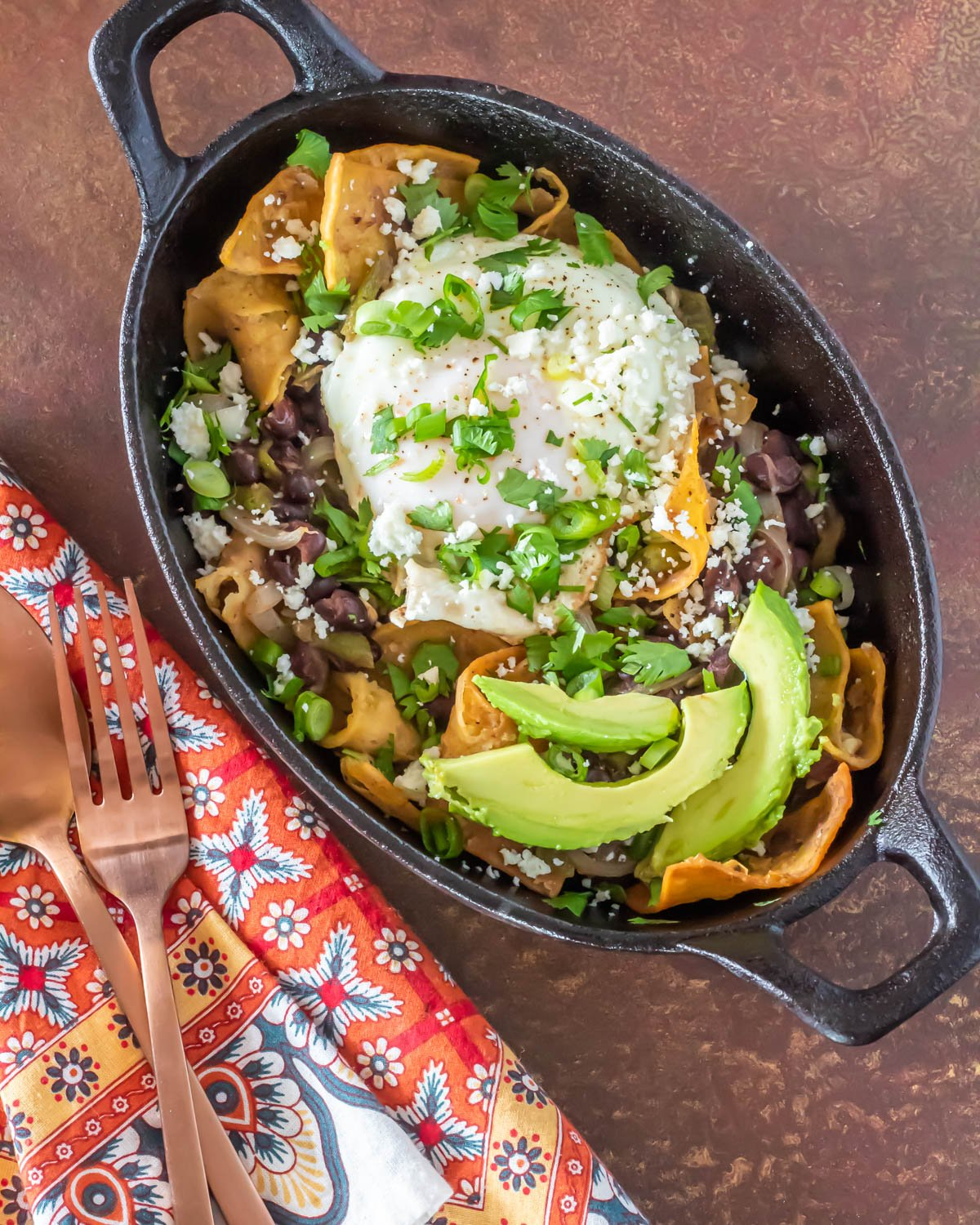 An oval black cast iron bowl with vegetarian black bean and green chile chilaquiles with a print napkin and copper fork.