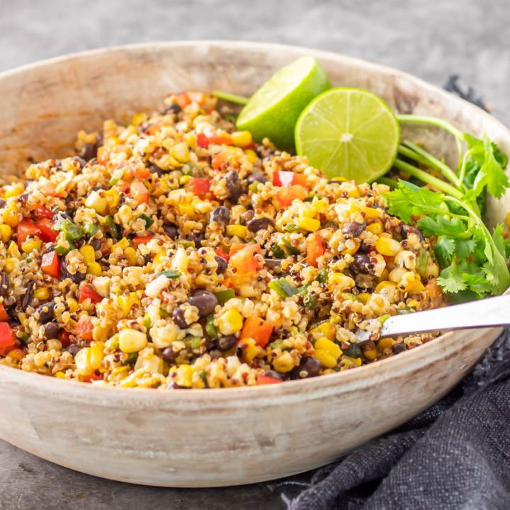 A white wood salad bowl with black bean and quinoa salad, lime, and cilantro.