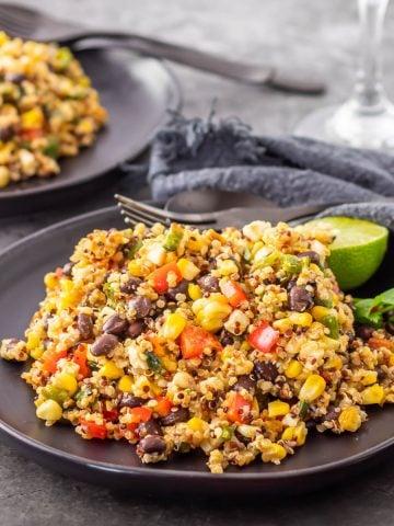 2 black plates with Mexican black bean and quinoa salad, black flatware, grey napkin.