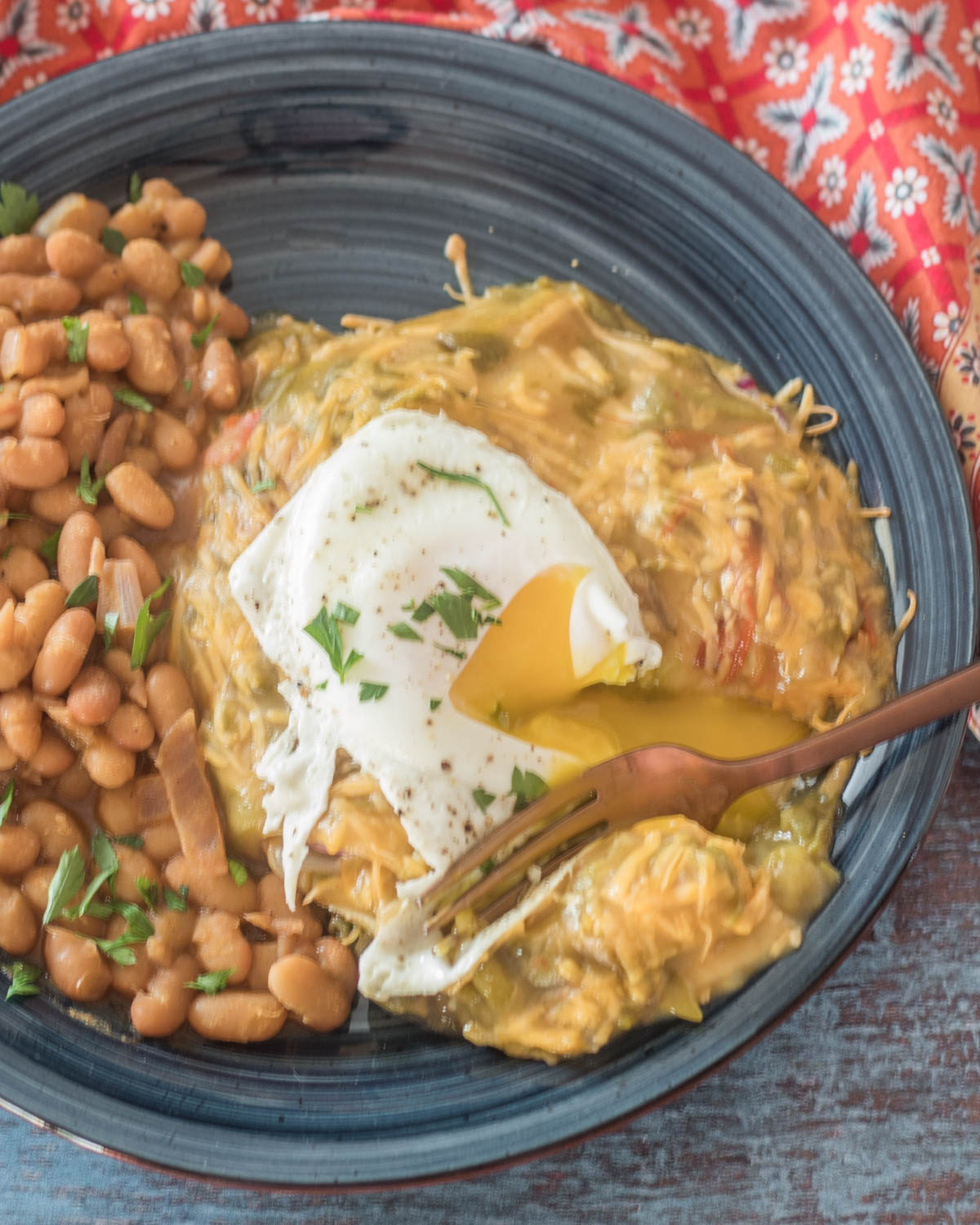 A blue ceramic plate with New Mexico green chile enchiladas with a broken yoke runny egg and beans.