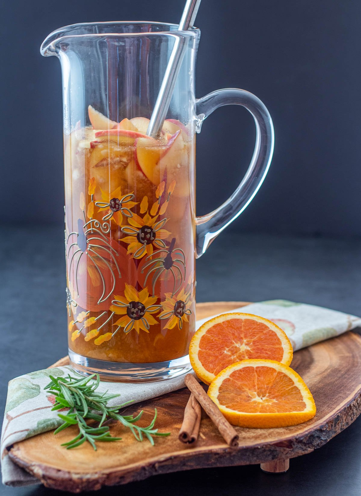 A glass pitcher with the sangria minus the ginger beer with garnishes.