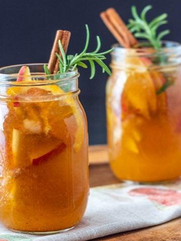 2 mason jars of fall pumpkin sangria garnished with rosemary and cinnamon stick.