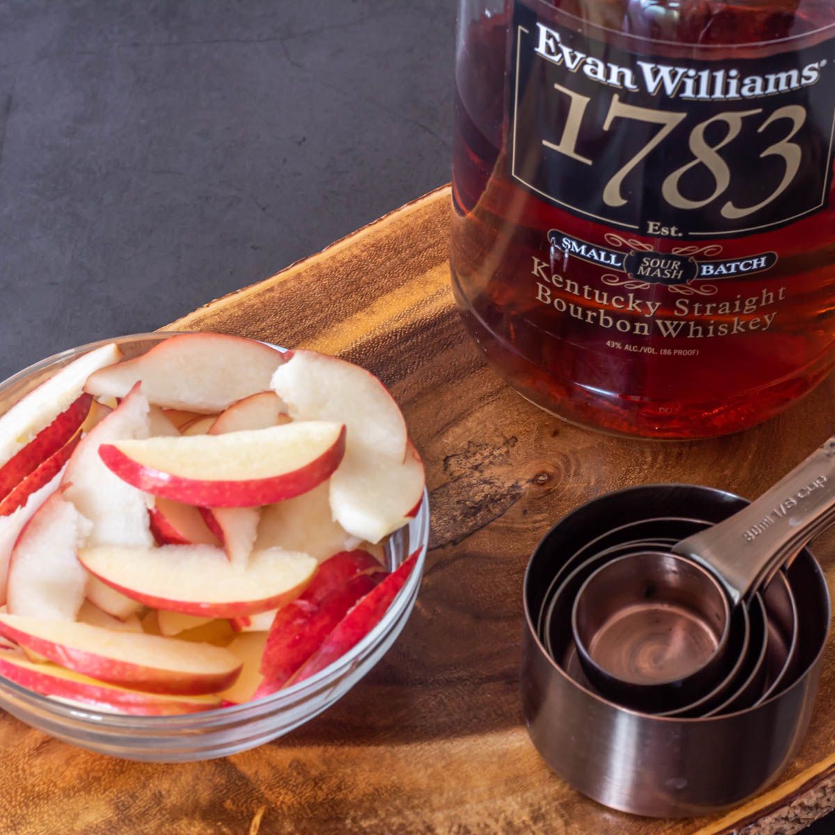 The fresh pear and apple sliced alongside a bottle of bourbon and measuring cups.