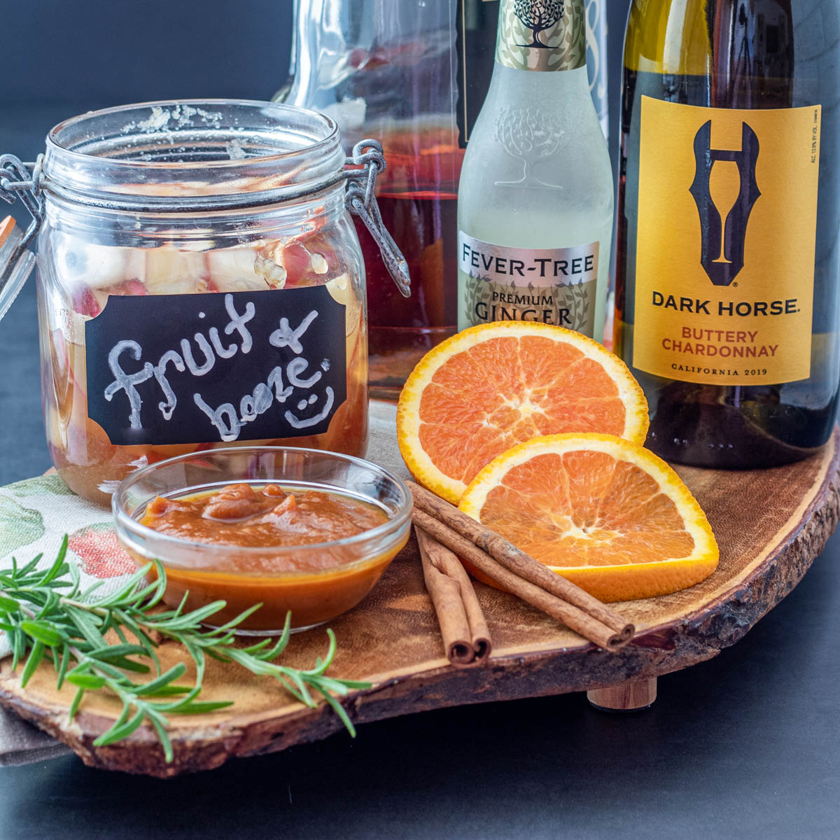 Ingredients for the fall sangria on a piece of wood: Pumpkin butter, fruit and bourbon, chardonnay, ginger beer, and sliced oranges.
