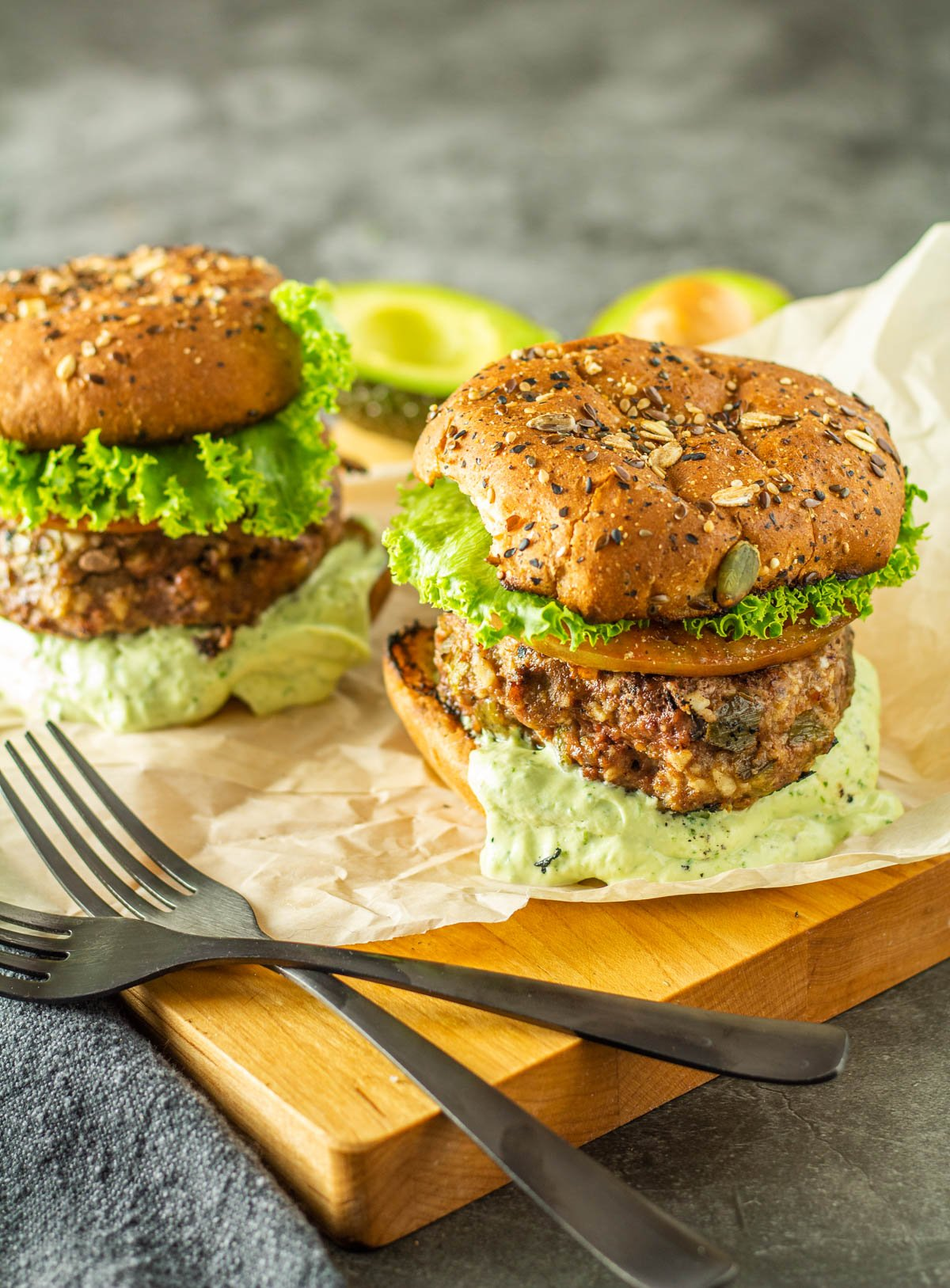 2 healthy bison burgers with whole grain buns on parchment on a wood cutting board.