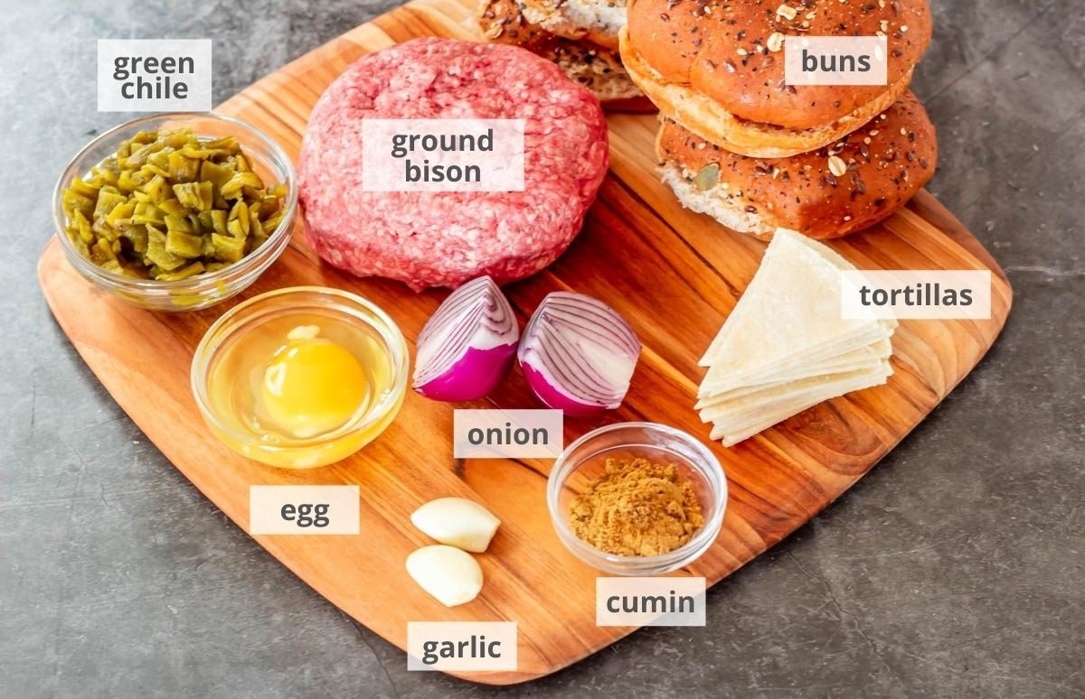 A wood cutting board with ingredients for healthy bison burgers: Ground bison, buns, tortillas, cumin, garlic, onion, egg, Hatch green chile.