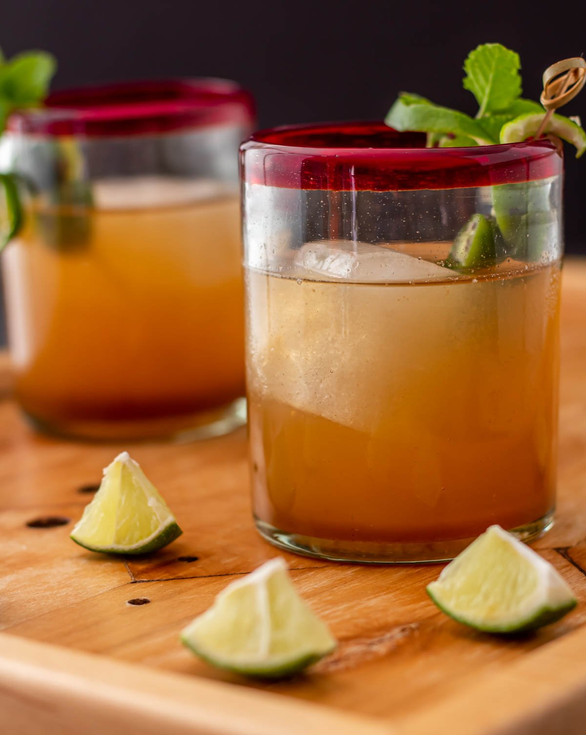 A straight on look at 2 red-rimmed rocks glasses with tamarind mezcal mules, lime wedges and garnish.