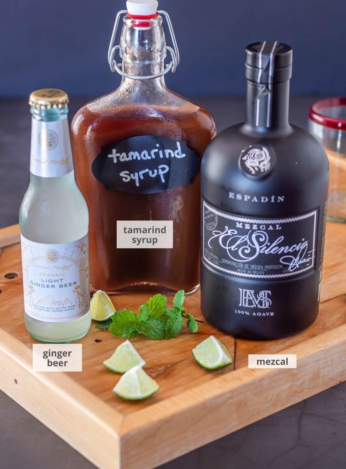 Ingredients for the tamarind mezcal mule: Ginger beer, tamarind syrup, mezcal, with lime and mint garnish.