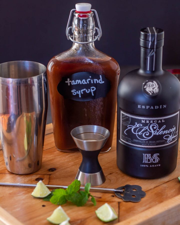 A bottle of mezcal, a bottle of tamarind syrup, a cocktail shaker, jigger, and bar spoon.