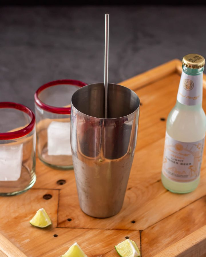 A stainless steel cocktail shaker and spoon, 2 rocks glasses with ice cubes, and a ginger beer.