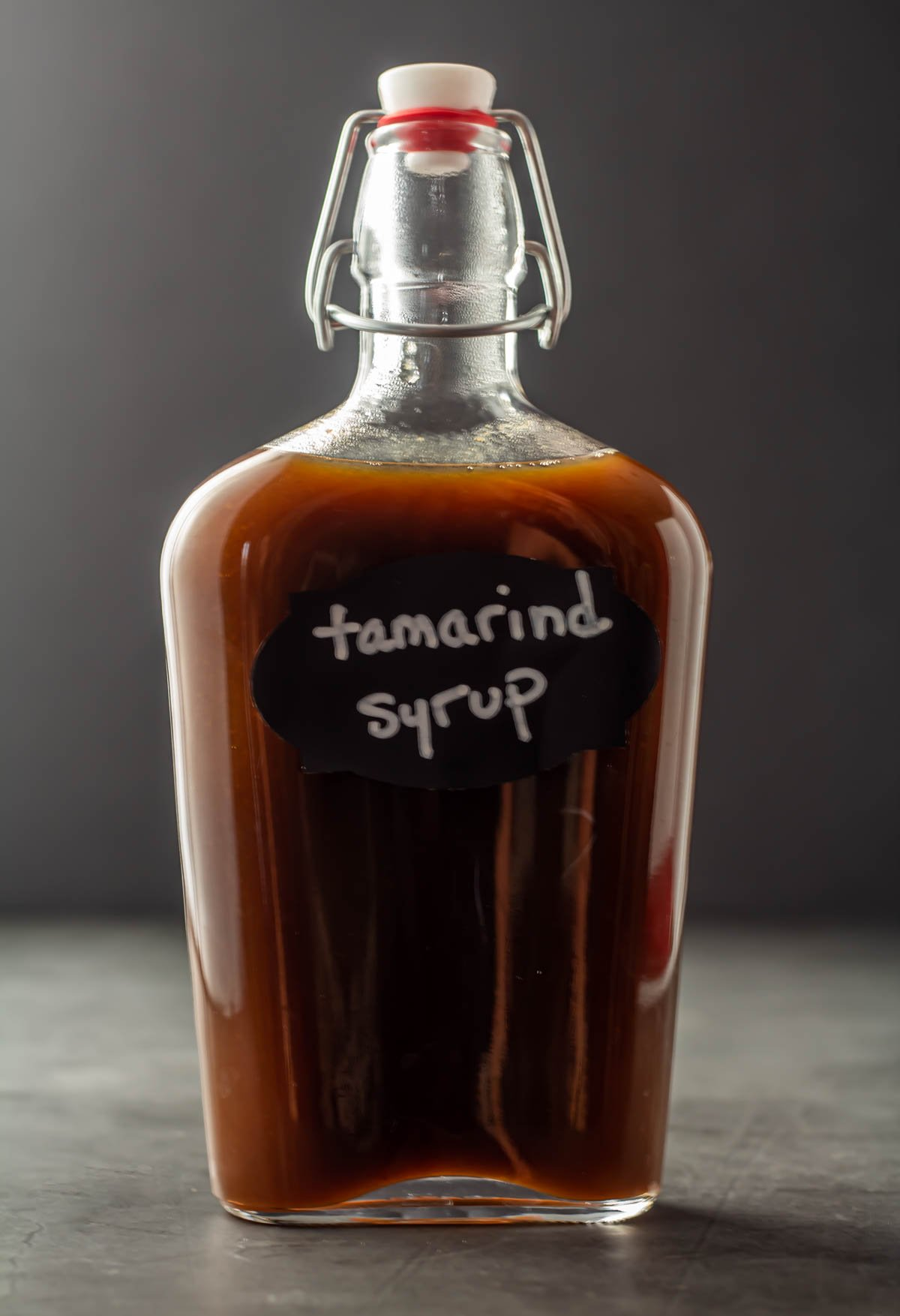 A tall glass bottle of tamarind syrup on a grey background.