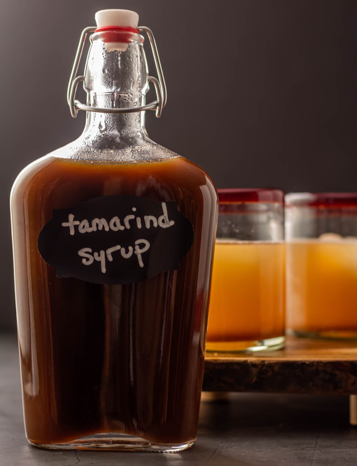 A glass bottle of tamarind syrup with 2 mezcal mules in the background.