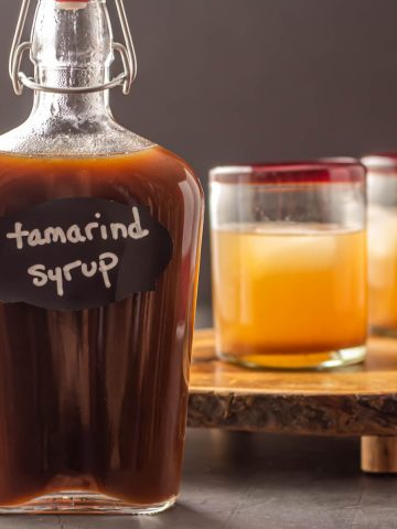 A glass bottle of tamarind syrup with two cocktails in the background.