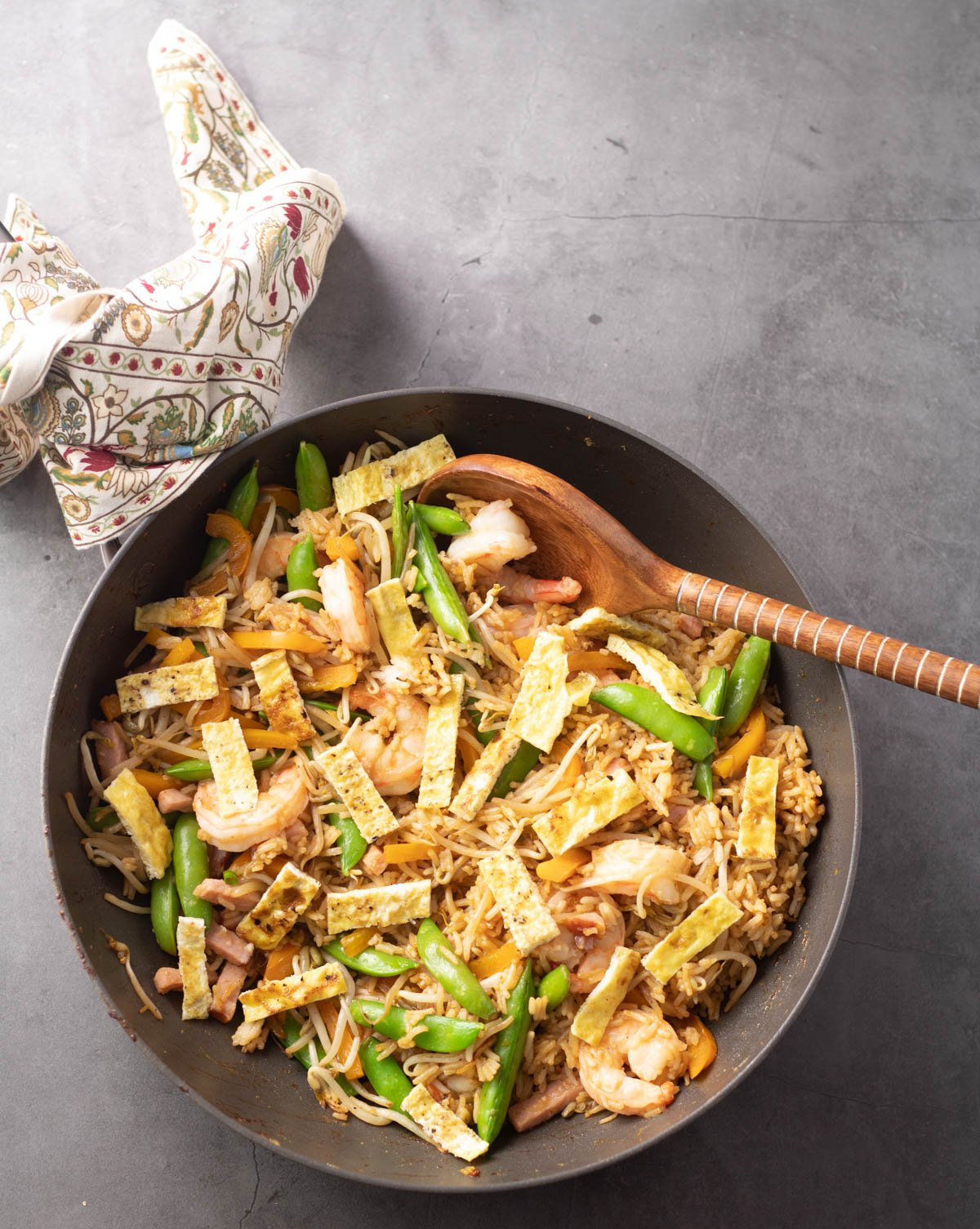 A wok with the completed fried rice, a wooden spoon, and a print napkin.