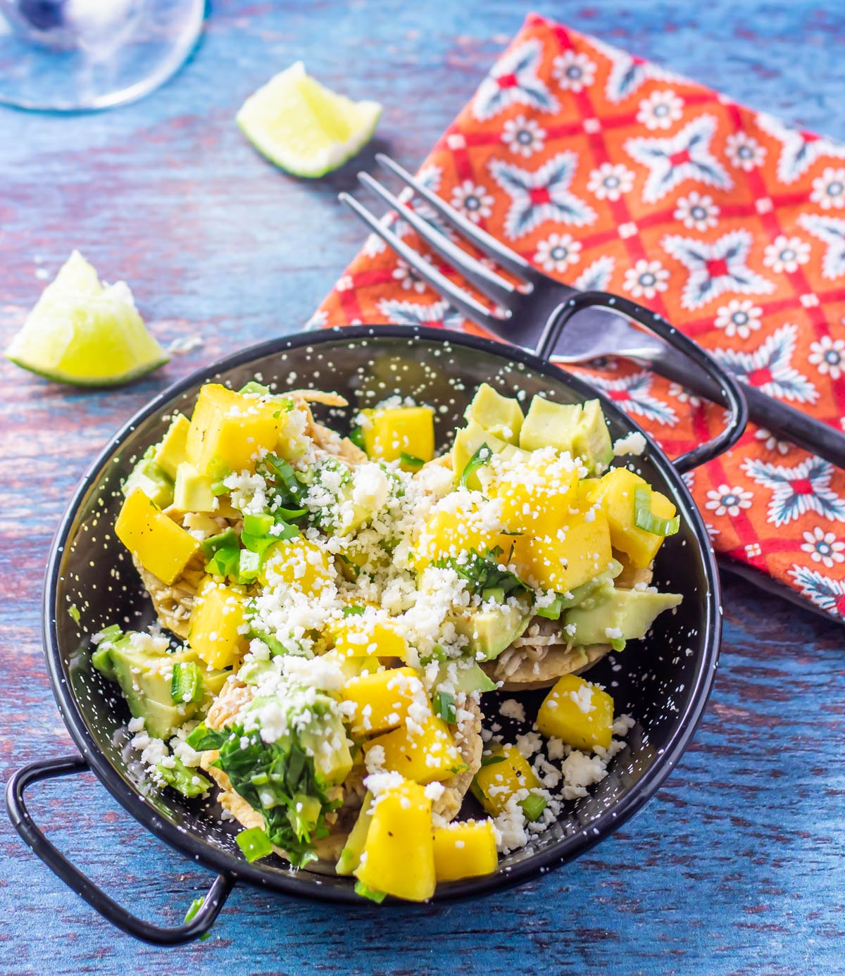 A mini paella pan with 3 sopas de pollo topped with mango salsa, avocado, and crumbled cotija, a print napkin and black fork.