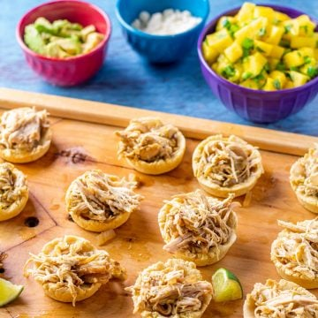 A tray of chicken sopes with mango salsa, avocado, and crumbled cotija in the background.