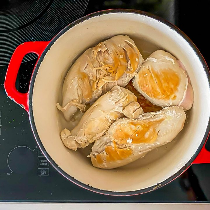 4 chicken breasts in a red cast iron pot being browned.