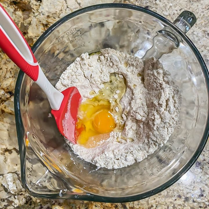 Ingredients for the sopes in a glass bowl: Masa flour, baking powder, salt, egg, and oil.