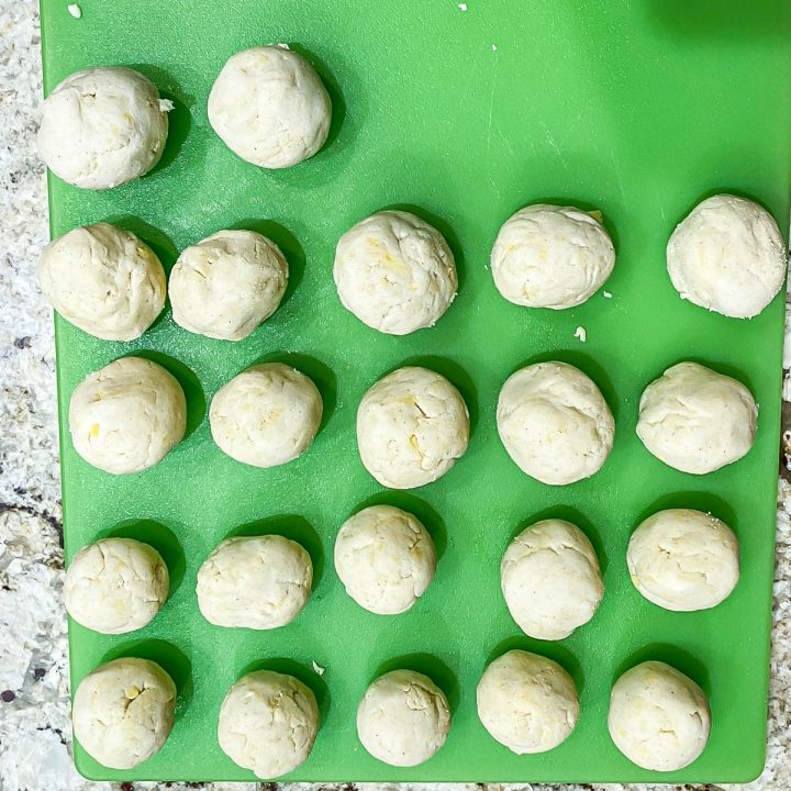 A green cutting board with 22 masa dough balls ready to be made into Mexican sopes.